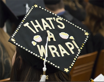 "A cap at a commencement ceremony that reads ""That's a wrap!,"" Communication Arts tile"
