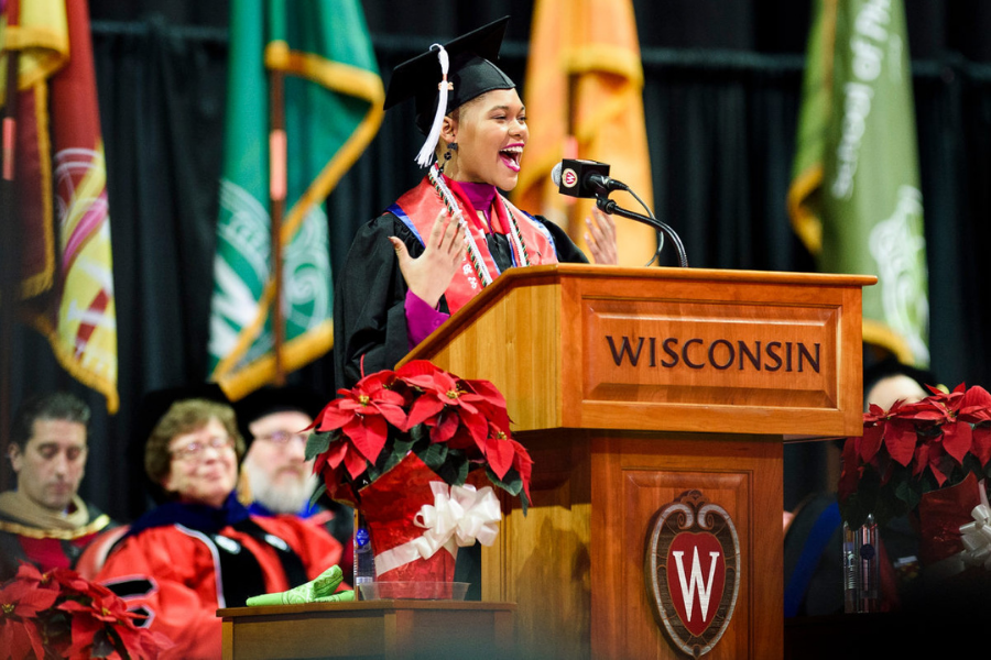 Female student dressed in commencement robe and cap addresses audience at podium