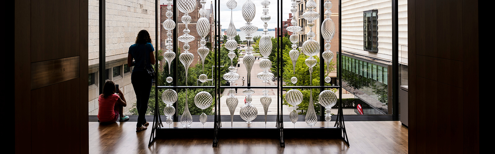 a display of blown glass ornaments before a window in the Chazen museum