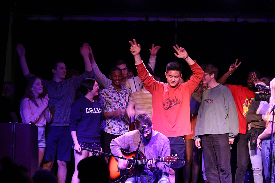 Students on stage hold their hands over their heads as a guitarist plays in front of the group