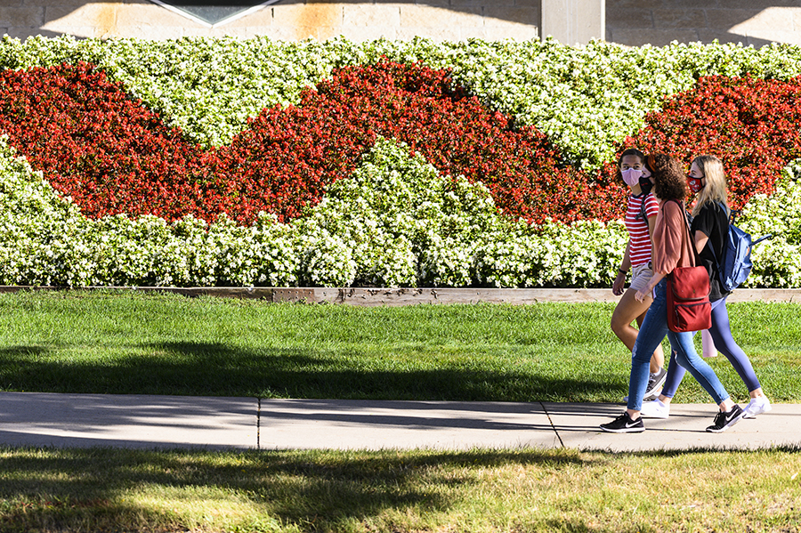 Students walk past campus landscaping with red W amid greenery