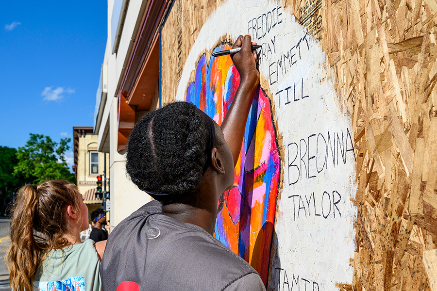Students paint a mural on plywood