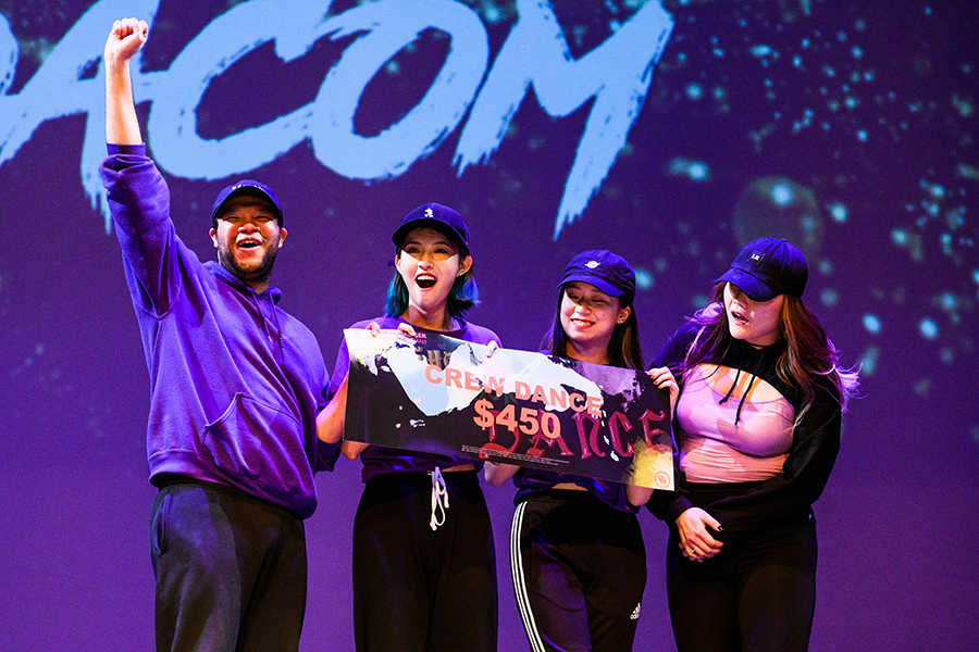 Four students stand on stage holding an award in front of a purple background