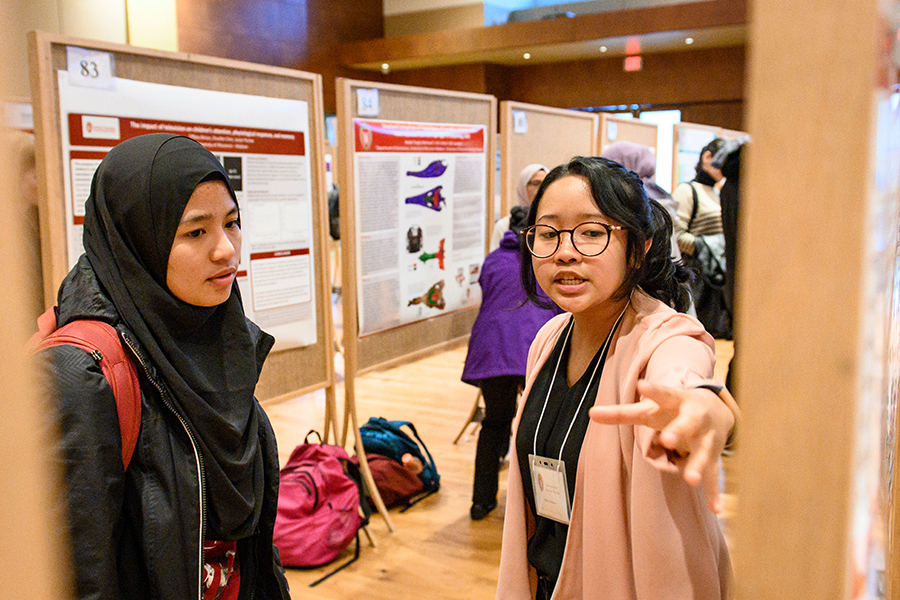 Students discuss their research project and poster display