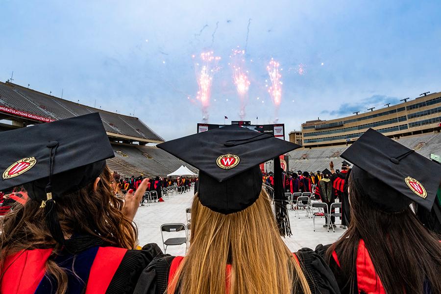 Three graduates watch a fireworks display
