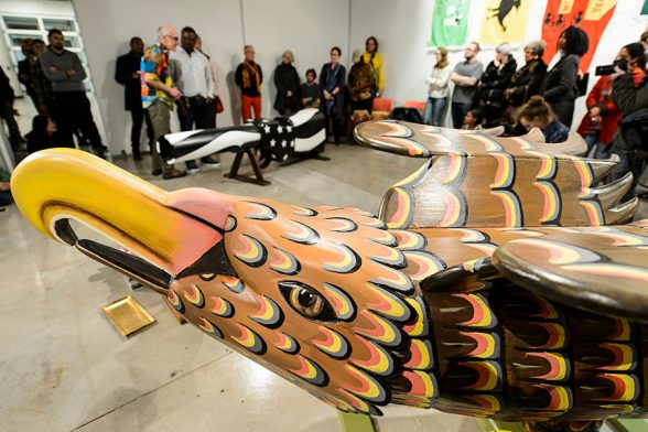 An eagle-shaped coffin fills the foreground within a gallery space